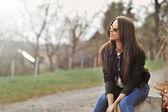 秋の公園で座っている魅力的な近代的な女性 — ストック写真