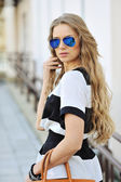 Elegant beautiful woman holding a bag in sunglasses — Stock Photo