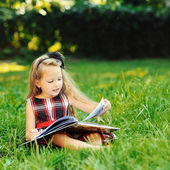 Sweet little girl reading book in a summer park  — Stock Photo