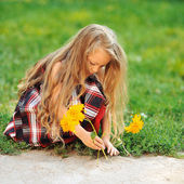 Cute little girl with flowers in a summer perk  — Stock Photo