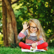 Cute little girl sits in a park. Reading book and hand gesture w — Stock Photo