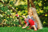 Photo of cute little girl sitting on green grass — Stock Photo
