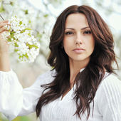 Beautiful young brunette woman standing near the apple tree - cl — Stock Photo