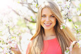 Beautiful young blonde woman standing near blooming tree — Stock Photo