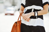 Fashionable woman with handbag in hands - close up — Stock Photo