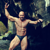 Portrait of a handsome muscular bodybuilder posing in a cave — Foto Stock