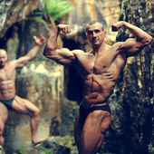Two bodybuilders posing in a cave  — Stock Photo