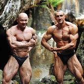 Two bodybuilders posing outdoors — Stock Photo