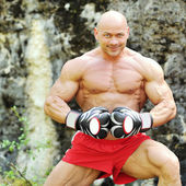 Muscular young man wearing boxing gloves — Stock Photo