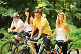 Group of attractive happy people on bicycles in the countryside — Stock fotografie