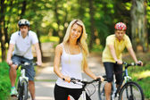 Portrait of attractive young woman on bicycle and two men in blu — 图库照片