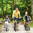 Happy family on a bicycles in the countryside — Stock Photo #45861097
