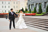 Happy bride and groom walking in an old town — Stock Photo