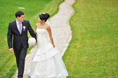 Bride and groom walking in a park together  — Stock Photo