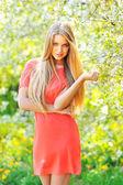 çiçek açan ağacın yanında duran güzel genç sarışın kadın — Stok fotoğraf