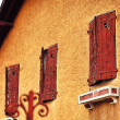 Old wood windows on a concrete house — Stock Photo