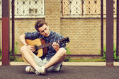 Teenage Boy plays an acoustic guitar — Stock Photo