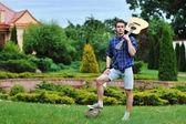 Junger mann mit akustik-gitarre im park — Stockfoto