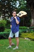Young man with acoustic guitar in park — Stock Photo