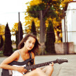 Young woman playing guitar on sunset — Stock Photo
