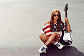 Beautiful and fashion young woman posing with electric guitar  — Stock Photo