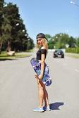 Beautiful young woman holding a skateboard — Zdjęcie stockowe