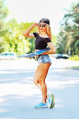 Beautiful young woman holding a skateboard — Stock Photo