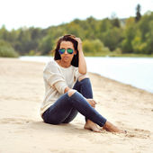 Young beautiful woman in sunglasses sitting on a beach — Stock Photo