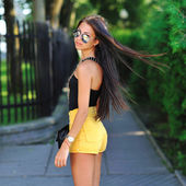 Sexy woman in sunglasses posing in a park — 图库照片
