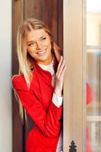 Beautiful young smiling blonde woman peeking out from behind the — Stock Photo