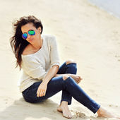 Beautiful brunette woman sitting on a sand  — 图库照片