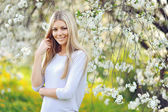 Beautiful spring girl in blooming tree — Стоковое фото