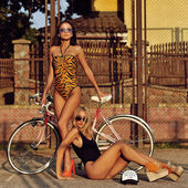 Young fashion models posing with a vintage bicycle — Stock Photo