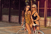 Two sexy women with vintage bike. Outdoor fashion portrait — Стоковое фото