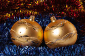 Yellow Christmas spheres with color tinsel — Stock Photo