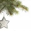 Silver star Christmas tree ornament hanging from a pine tree branch isolated against white — Stok fotoğraf