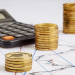 Stock Photo: Coins stocks rising, calculator on financial charts