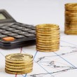 Coins stocks rising, calculator on the financial charts — Stock Photo #22763176