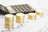 Downtrend stacks of coins, a calculator on the financial chart. — Stock Photo