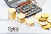 Downtrend stacks coins, calculator, glasses and dices cubes with — Stock Photo
