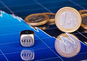 Close-up dices cube with the word SELL, one-euro coins and downt — Stock Photo