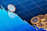 One-euro coins on downtrend chart. Selective focus — Stock Photo