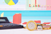 Dices cube with the word SELL, one-euro coin, calculator and f — Stock Photo