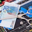 Scissors cutting euro banknote, dices cube with the word STOP. — Stock Photo