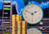 Downtrend stacks of golden coins, clock and the financial chart — Stock Photo