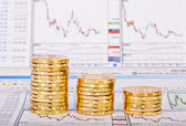 Down trend stacks of golden coins and financial chart as the bac — Stock Photo