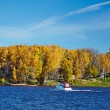 Power boat on an autumn lake in sunny day — Stock Photo