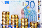Downtrend stacks of golden coins and euro banknote as background — Stock Photo