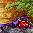 Christmas decoration. Red ball with violet ribbon, fir-tree and  — Stock Photo