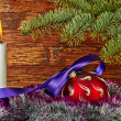 Christmas decoration. Red ball, violet ribbon, fir-tree, candle  — Zdjęcie stockowe